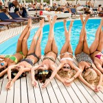 happy girls on the beach. beautiful girlfriends lie on white wooden floor near the pool. girls lying on their backs and show their legs